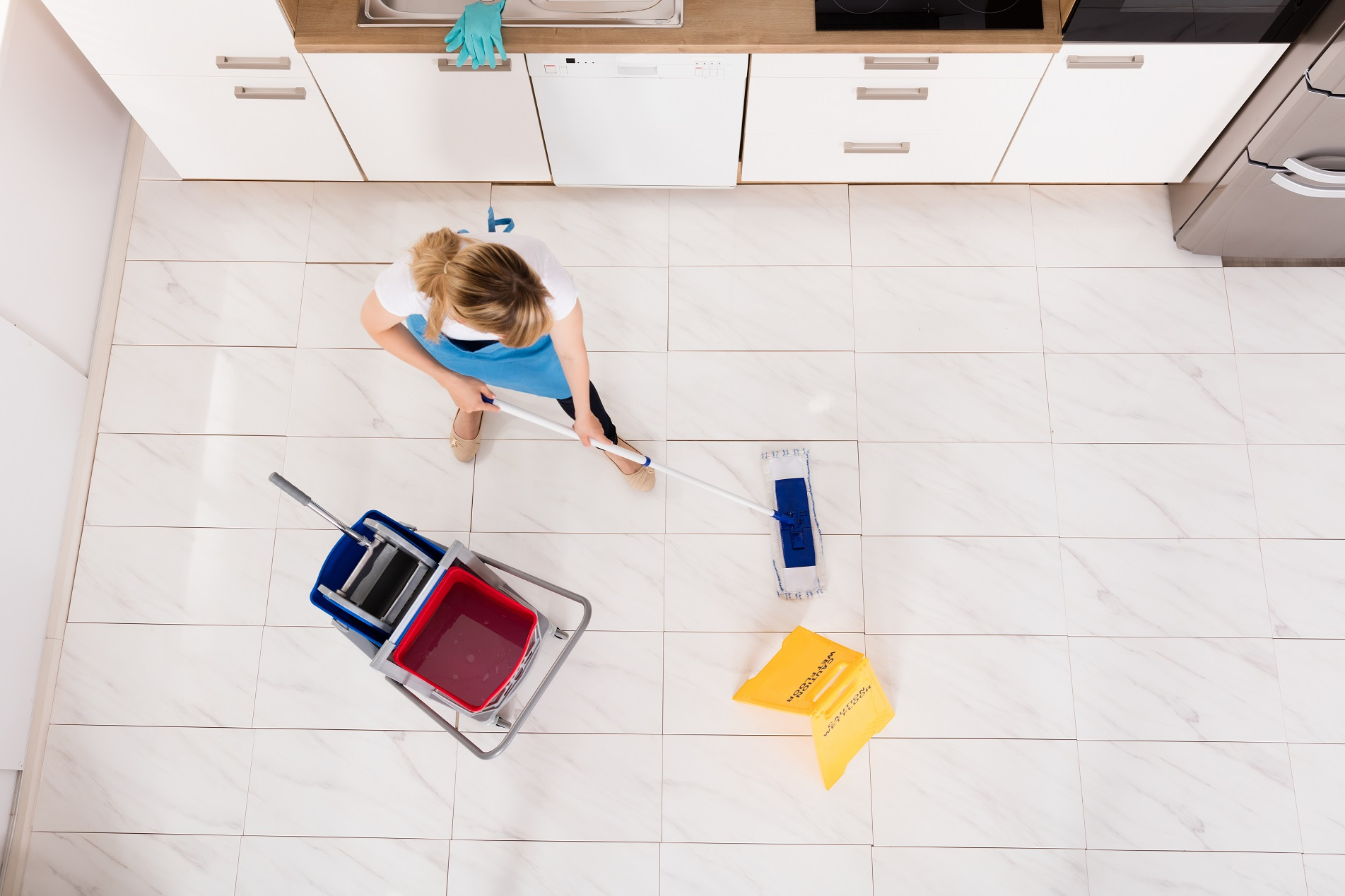 Housemaid Mopping Floor In Kitchen